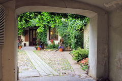 Arch in old village house, small yard and flowers Royalty Free Stock Photo