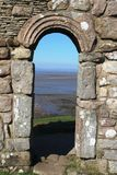 Arch over doorway at St Patrick's Chapel, Heysham. View out over Morecambe Bay looking through an archway in the ruins of St Patrick's Chapel which stands on a Royalty Free Stock Images
