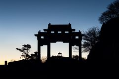 Arch and pavilion in silhouette on the summit of Taishan, China. TAISHAN, CHINA - JAN 1, 2014 - Arch and pavilion in silhouette on the summit of Taishan, China royalty free stock photo