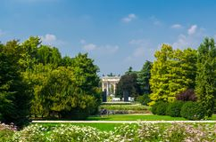 Arch of Peace gate and green trees, grass lawn in park, Milan, I stock photography
