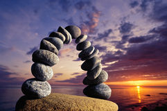 Arch of pebbles. Balancing of pebbles on the boulder in the evening Stock Images