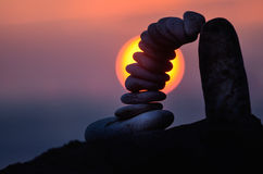 Arch of pebbles. Balancing of pebbles on the boulder in the evening Royalty Free Stock Images