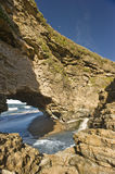 Arch Rock Formaton leading into the ocean. Arch Rock and little waterfall leading into the ocean royalty free stock images