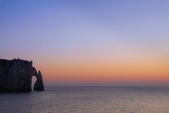Arch in the sea in Normandy coast in France. View of the famous arch of Etretat in Normandy coast in France during the golden hour Stock Images