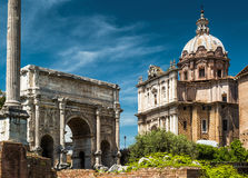 Arch of Septimius Severus and medieval church in Roman Forum, Ro. Triumphal arch of the emperor Septimius Severus and medieval church of Santi Luca e Martina in Stock Photography