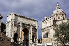 Arch of Septimius Severus with Saints Luca and Martina church. Ancient Arch of Septimius Severus and Saints Luca e Martina baroque church in Roman Forum with Royalty Free Stock Image