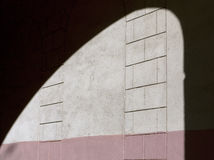 Arch shadow on plaster color wall texture. Stock Photography