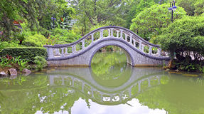 Arch shape stone bridge in garden Stock Photos