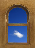Arch shaped wood window frame with white cloud in blue sky. Arch shaped wood window frame with view of blue sky and one white cloud Stock Photos