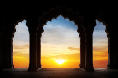 Arch silhouette at sunset. Indian arch silhouette in old temple at dramatic orange sunset sky background. Free space for text Royalty Free Stock Photo