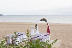 Arch for on-site registration is decorated with flowers and white cloth. Wedding ceremony on the Bay. Close up. Flowers. Bouquet stock images