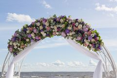 Arch for on-site registration is decorated with flowers and white cloth. Wedding ceremony on the Bay. Close up. Flowers. Bouquet royalty free stock image