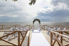 Arch for on-site registration is decorated with flowers and white cloth. Wedding ceremony on the Bay. Close up. Flowers. Bouquet stock photography