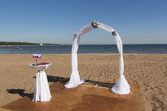 Arch for on-site registration is decorated with flowers and white cloth. On the Desk of the Registrar is the Russian flag royalty free stock image