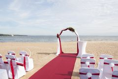 Arch for on-site registration is decorated with flowers and white cloth. Wedding ceremony on the Bay stock image