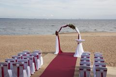 Arch for on-site registration is decorated with flowers and white cloth. Wedding ceremony on the Bay stock photo
