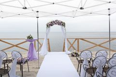 Arch for on-site registration is decorated with flowers and white cloth. Wedding ceremony on the Bay royalty free stock image