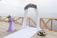 Arch for on-site registration is decorated with flowers and white cloth. Wedding ceremony on the Bay royalty free stock images