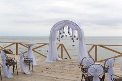Arch for on-site registration is decorated with flowers and white cloth. Wedding ceremony on the Bay. Close up. Flowers. Bouquet stock photos