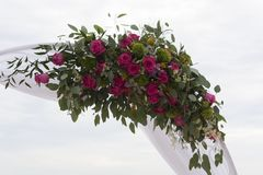 Arch for on-site registration is decorated with flowers and white cloth. Wedding ceremony on the Bay. Close up. Flowers. Bouquet royalty free stock images