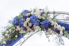 Arch for on-site registration is decorated with flowers and white cloth. Wedding ceremony on the Bay. Close up. Flowers. Bouquet stock photo