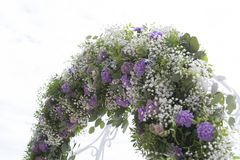Arch for on-site registration is decorated with flowers and white cloth. Wedding ceremony on the Bay. Close up. Flowers. Bouquet stock image