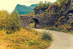 Arch in a stone bridge over a mountain road. Stone arch over the road. Beautiful nature stock photography