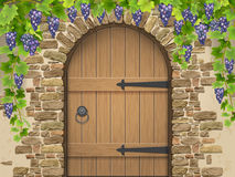 Arch of stone grapes and wooden door Royalty Free Stock Images