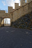 Arch in the stone wall. And road passes through in it Royalty Free Stock Photos