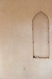 Arch in Stucco wall. An arch inset in a stucco wall, with an outlet and a lighting fixture stock photography