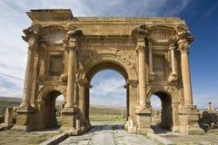 The Arch of Trajan. Algeria. Timgad (ancient Thamugadi or Thamugas). Paving stones of Decumanus Maximus street and 12 m high triumphal arch, called Trajan's Arch Stock Photography
