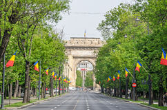 The Arch of Triumph Arcul de Triumf from Bucharest Romania. International Day with romanian flags, view from Kisseleff Avenue Stock Image