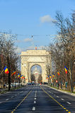 The Arch of Triumph Arcul de Triumf from Bucharest Romania. National Day with romanian flags, view from Kisseleff Avenue Stock Images