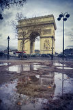 Arch of triumph and a puddle. Arch of triumph at the end of the Champs Elysees reflecting in a puddle in Paris, France Royalty Free Stock Photography
