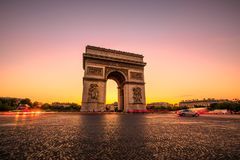 Arc de Triomphe Sunset. Arch of triumph at twilight. Arc de Triomphe at end of Champs Elysees in Place Charles de Gaulle with cars and trails of lights. Popular Stock Photography