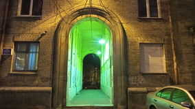 Arch and a tunnel flooded with green light stock image
