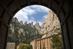 Arch view of jagged mountains in Catalonia, Spain, showing the Benedictine Abbey at Montserrat, Santa Maria de Montserrat, near Ba Royalty Free Stock Photography