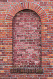 Arch in a wall made from red bricks.  Stock Photography