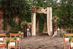 Arch for the wedding ceremony, decorated cloth flowers greenery,. Arch for the wedding ceremony, decorated with cloth flowers and greenery, is in a pine forest Royalty Free Stock Photos