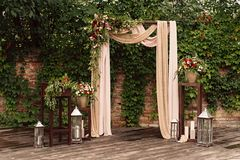 Arch for the wedding ceremony, decorated cloth flowers greenery,. Arch for the wedding ceremony, decorated with cloth flowers and greenery, is in a pine forest Royalty Free Stock Photography