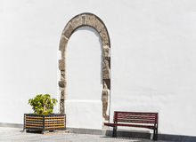 Arch on a white stucco wall. Former entrance in the form of an arch on the wall covered with white stucco finishing with a bench and a square pot with plant on Royalty Free Stock Images