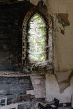 Arch Window with Cobwebs - Abandoned Church. A vertical interior view of an cobwebbed arch window looking out at ivy and other vegetation at a long closed and Royalty Free Stock Photos