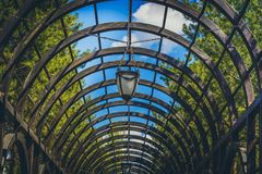 Arch from a wooden brown beam with lanterns against a background of green trees. And a blue sky with clouds Stock Photos