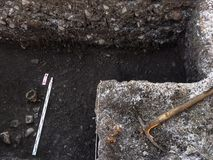 Archaeological excavation with skull still half buried in the ground and tools lying beside royalty free stock photos