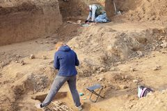 Archaeological excavations. The archaeologists in a digger process, researching the tomb with human bones, drawing the human remai royalty free stock images