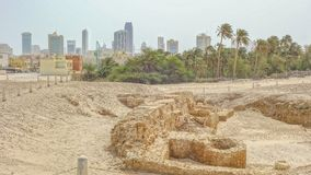 Archaeological excavations and Manama skyline, Qal`at al-Bahrain royalty free stock image