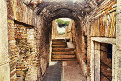 Archaeological excavations of Ostia Antica:Inside a ruin with arch and paved road. Archaeological excavations of Ostia Antica: Inside a ruin with arch and paved Royalty Free Stock Photography