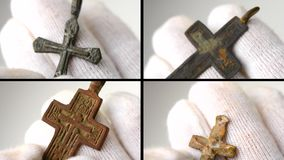 4 in 1. Archaeological find Christian pectoral cross close-up in hands. With white gloves. Crucifix archaeological find. Multicam split screen group video wall stock video