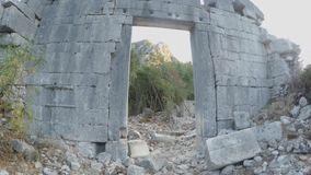 Archaeological reconstruction of the ancient wall and coniferous trees in the ruins of the city`s antiquity in the mountains in th. Ruins of the ancient city of stock footage