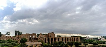 Archaeological ruins of the Severian Arcades on the Palatine and. Temple of Apollo Palatine with a sky with many clouds. View from the street called `Viale Stock Image